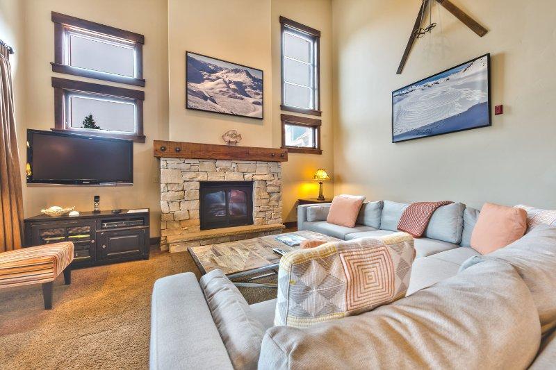 Salon spacieux avec sièges confortables, télévision, foyer au gaz et accès à la terrasse