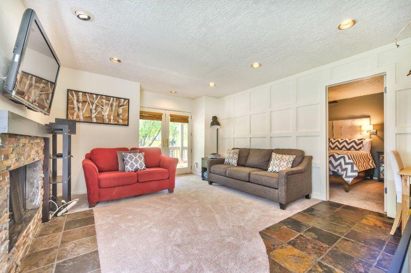 Área de estar com TV de tela plana, DVD, lareira a gás, sofá-cama queen e acesso ao convés