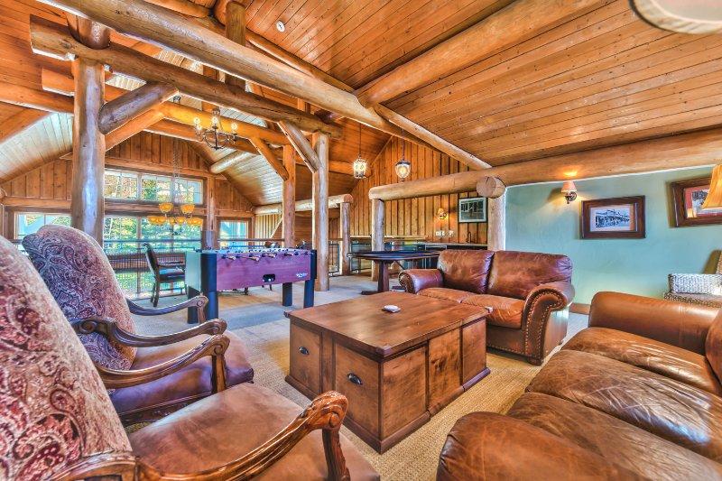 Spacieuse salle de jeux en mezzanine avec table de poker, baby-foot et table de jeu, un bar et des sièges confortables