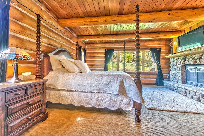 Grande chambre de maître au premier niveau avec un lit king-size, une télévision à écran plat, une cheminée et une salle de bains privée