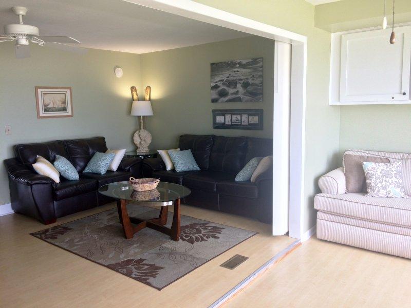 Mesa y sillas y sofás cama en habitación solar y sala de estar.
