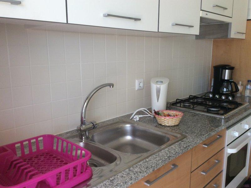Cuisine avec four, plaque de cuisson, lave-linge, lave-vaisselle, micro-ondes, machine à café, une bouilloire et un grille-pain.