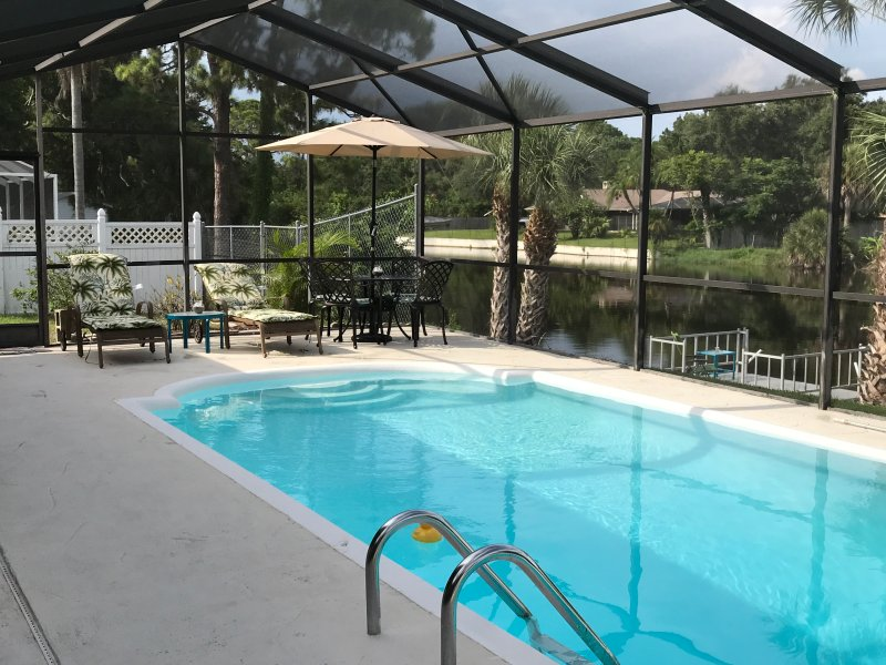 Large Heated Pool with sitting and dining table by the lake and fishing dock