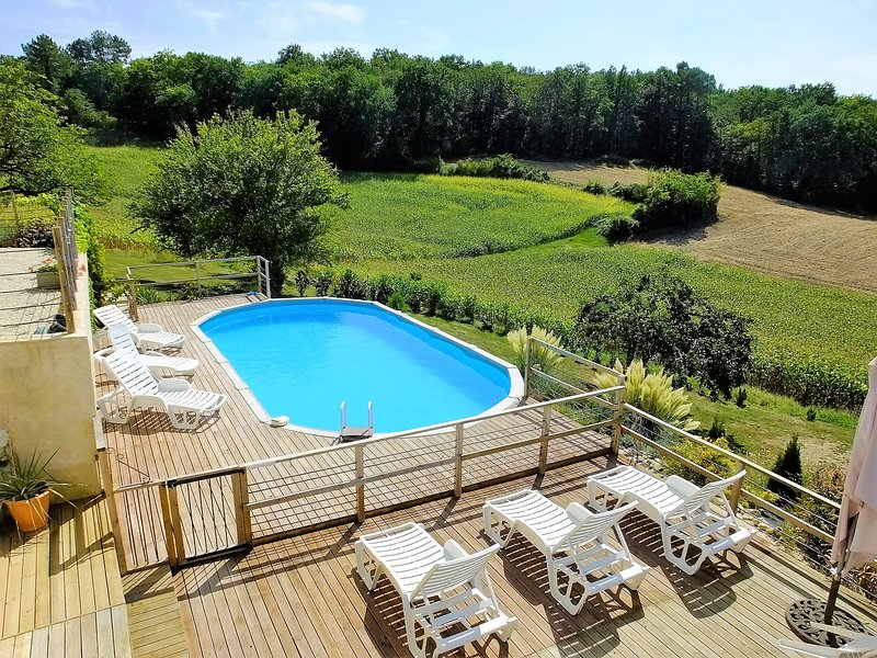 Pool with views to the left over fields and woodland.