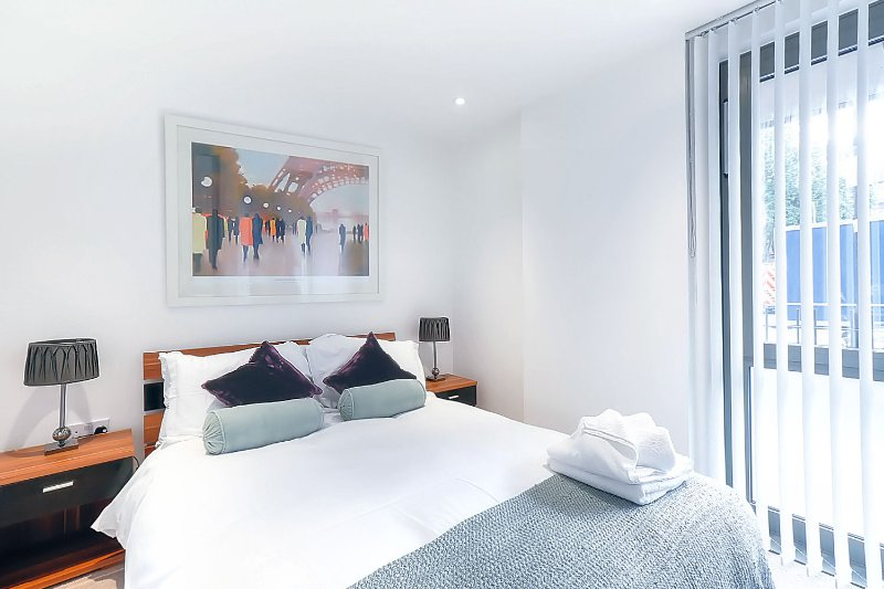 The tranquil bedroom opens up through a hall into the living area where there's a double sofa bed.