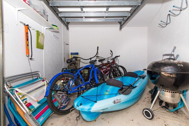 salle de magasin avec des vélos et un kayak double, un barbecue et quelques chaises de plage pour nos clients à utiliser