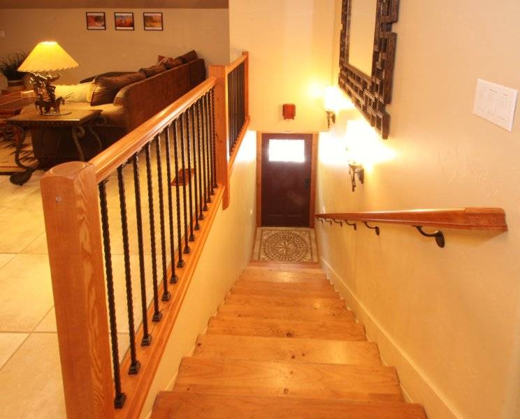 Entrance with knotty pine stairs and custom railing