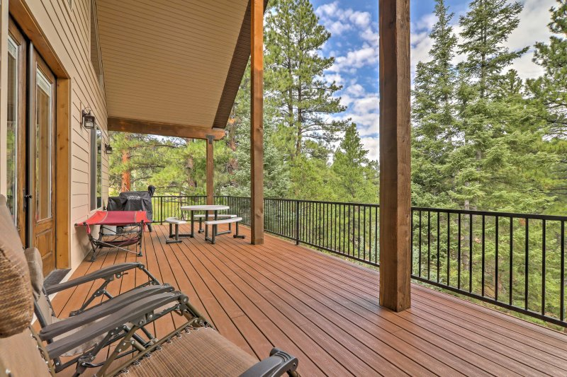 The property features an expansive deck that overlooks the surrounding forest.