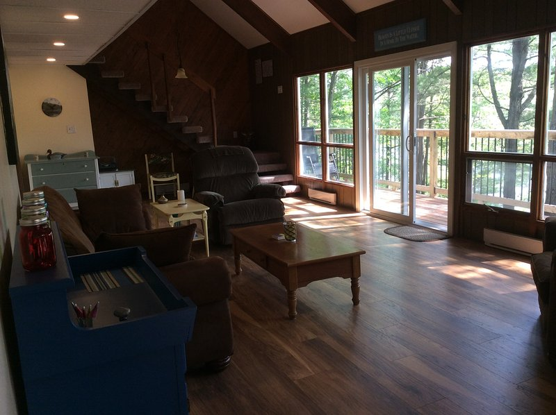 sala de estar con puertas que dan a la cubierta del agua y los árboles con vistas