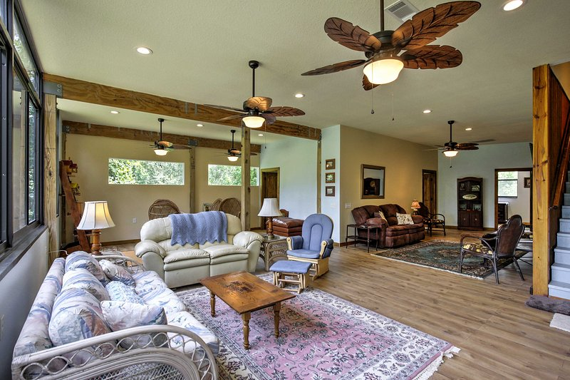 The spacious living area features comfortable furniture, numerous windows and ceiling fans.