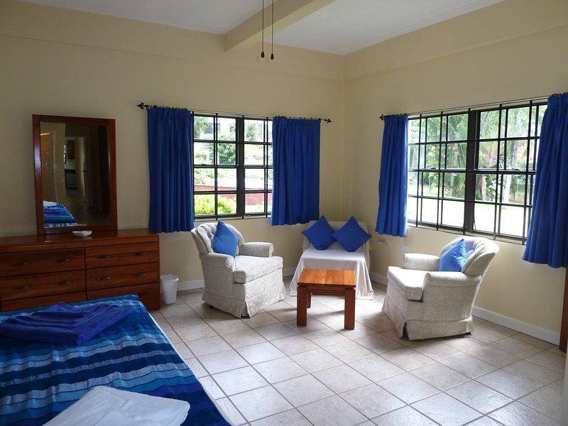 Seating area of master bedroom with door leading to verandah