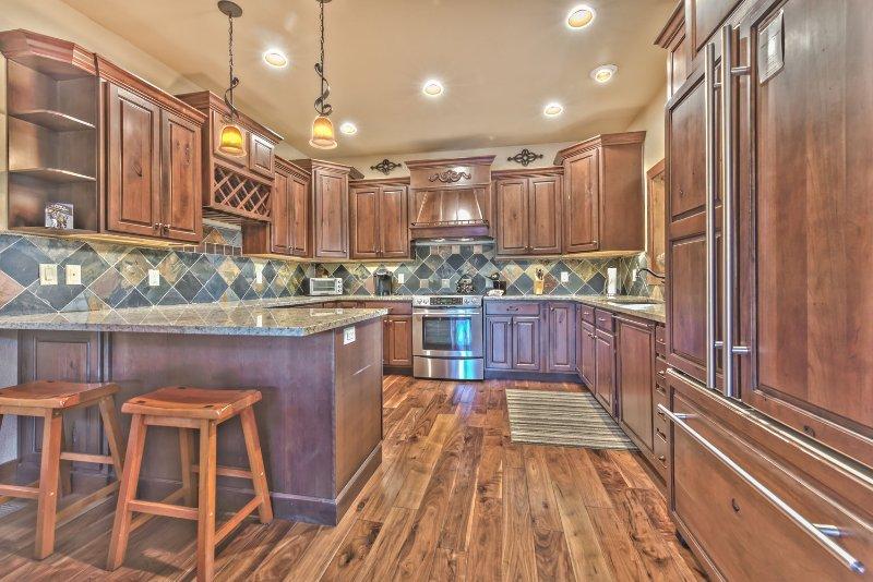 Cocina completamente renovada con electrodomésticos de acero inoxidable, acabados de alta gama, encimeras de granito y asientos de bar