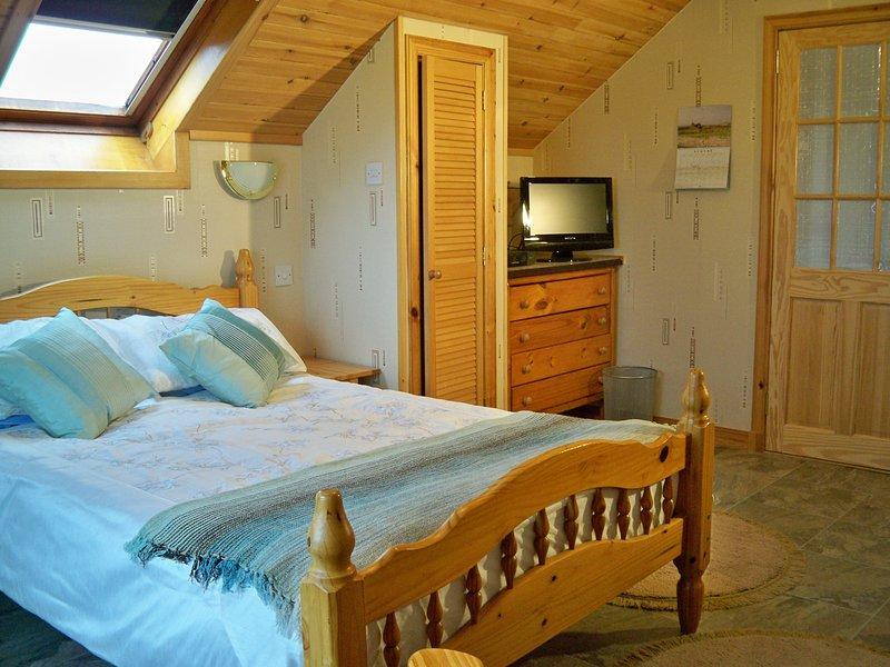 Habitación grande y bien climatizada con una cama doble, armarios empotrados, cómoda y sofá y sillas.