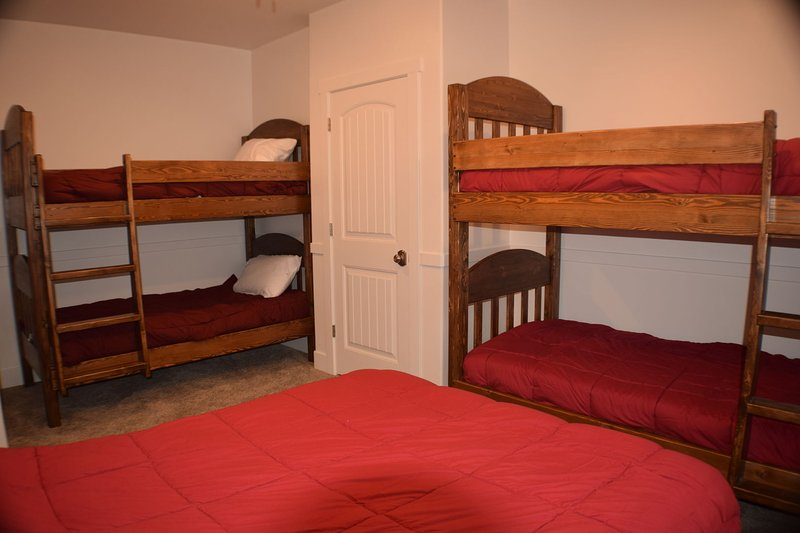 Bedroom with queen bed and two twin bunk sets