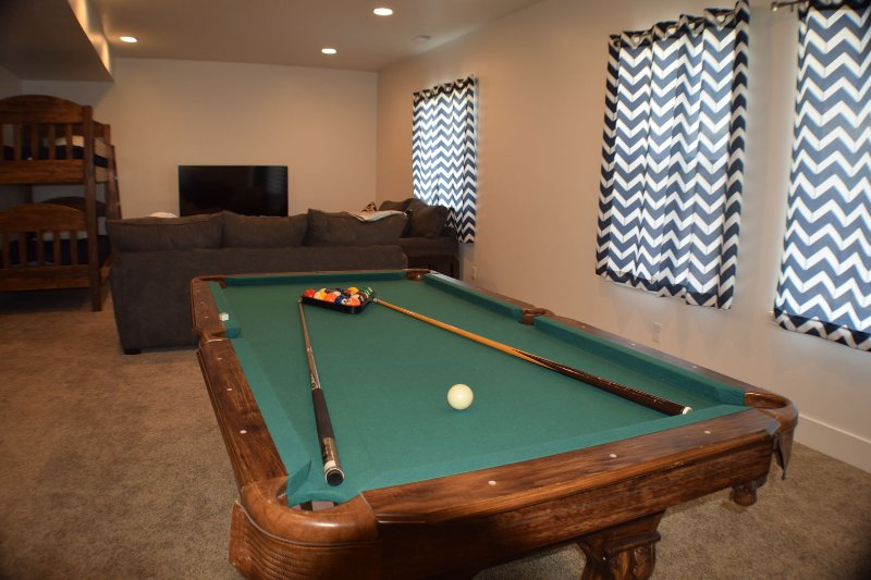 Lower sitting area and game room with pool table, air hockey, and basketball