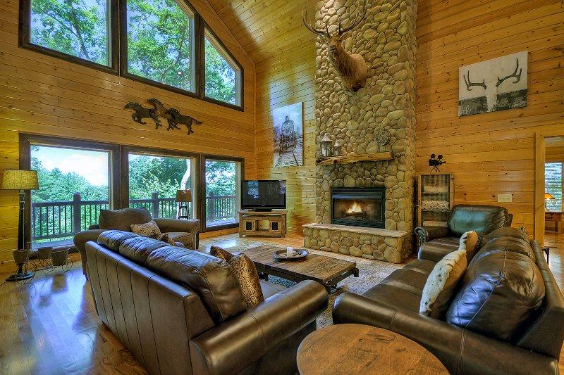 Spacieuse, Salon / Salle de séjour confortable avec plancher cheminée en pierre de plafond.