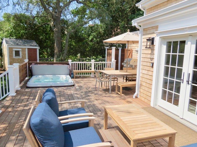 Banheira de hidromassagem, mesa, churrasqueira, chuveiro ao ar livre e sala de estar