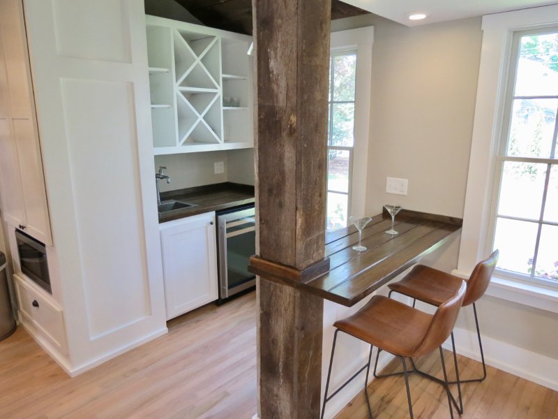 Área de bar é apenas fora da cozinha com um centro de bebidas e balcão de madeira personalizado