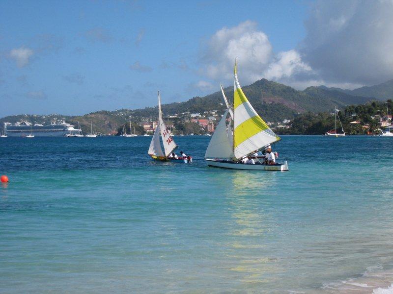 Barche a vela sul mare cristallino con la capitale St George's in background.
