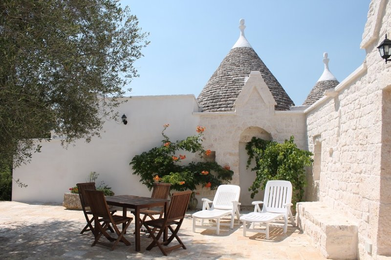 Trullo San Salvatore courtyard above pool with loungers and garden table and chairs.
