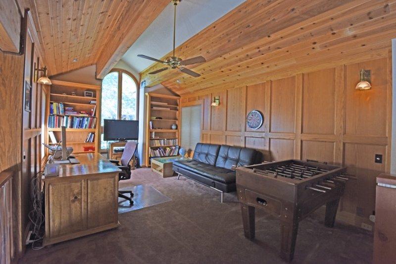 loft no andar de cima com uma mesa de pebolim, TV e espaço na mesa
