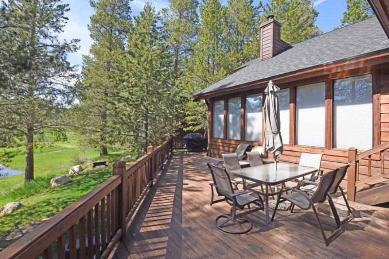 espaço deck ao ar livre com mobiliário e uma churrasqueira com vista para um pequeno riacho