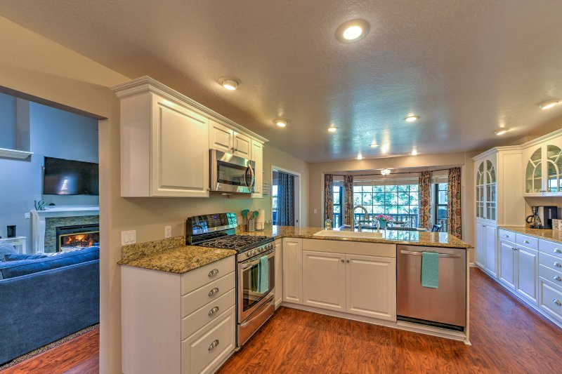 The kitchen features stainless steel appliances and sleek white cabinetry.