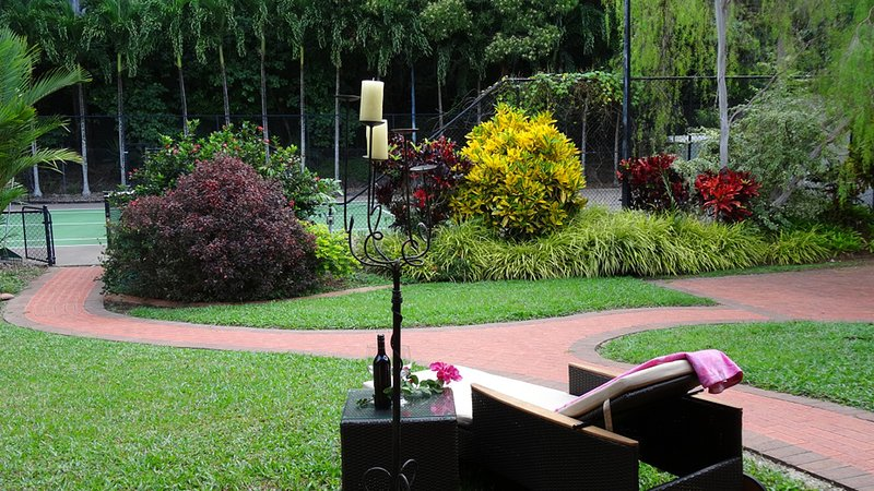 Relax on the recliner lounge by the tennis court.