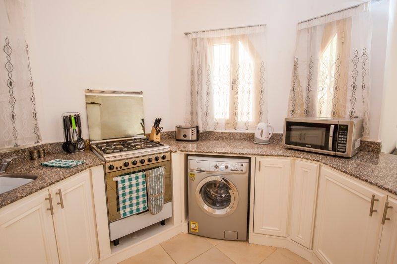 Cuisine entièrement équipée, avec cuisinière complète, lave-linge, réfrigérateur-congélateur, micro-ondes, grille-pain, etc.