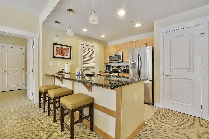 Luxury Bar Stools, customs sink, refrigerator and Stove.