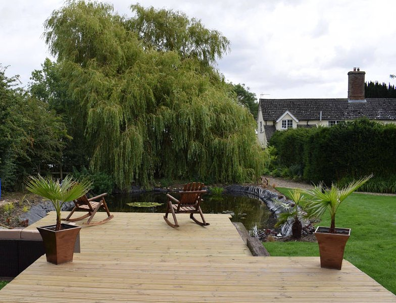 Beautifully landscaped garden with decking over the pond