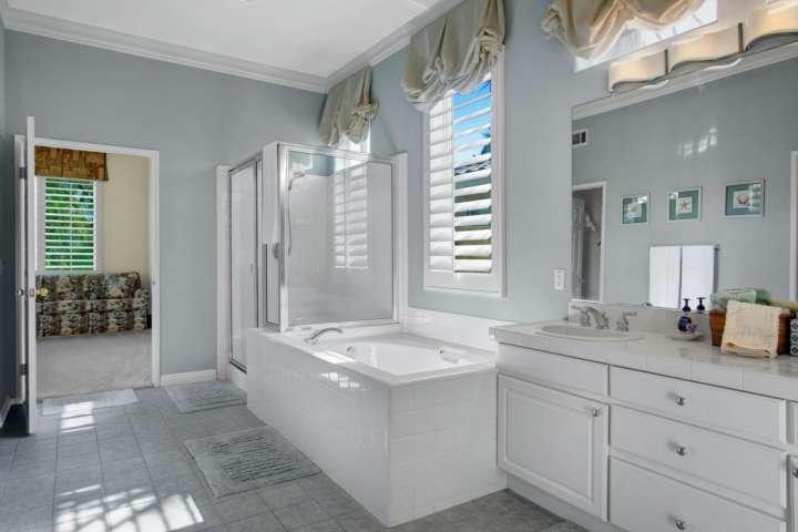 Enorme meester badkamer met dubbele wastafel, bad, inloopdouche, en inloopkast
