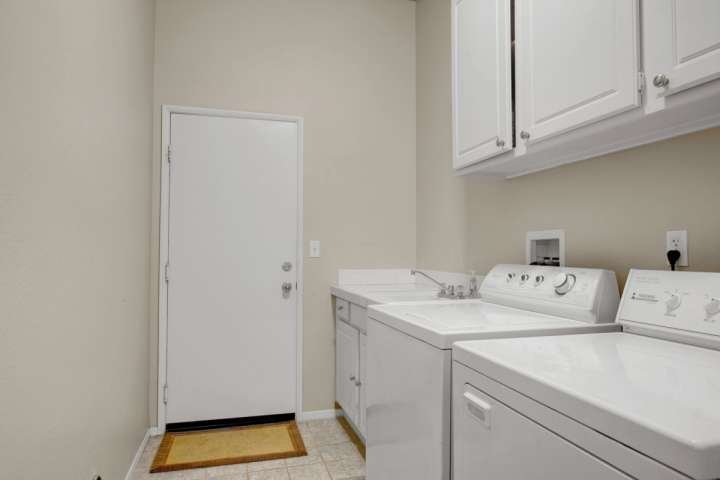 Full size wasmachine en droger in de wasruimte. Komt uit op 2 auto garage