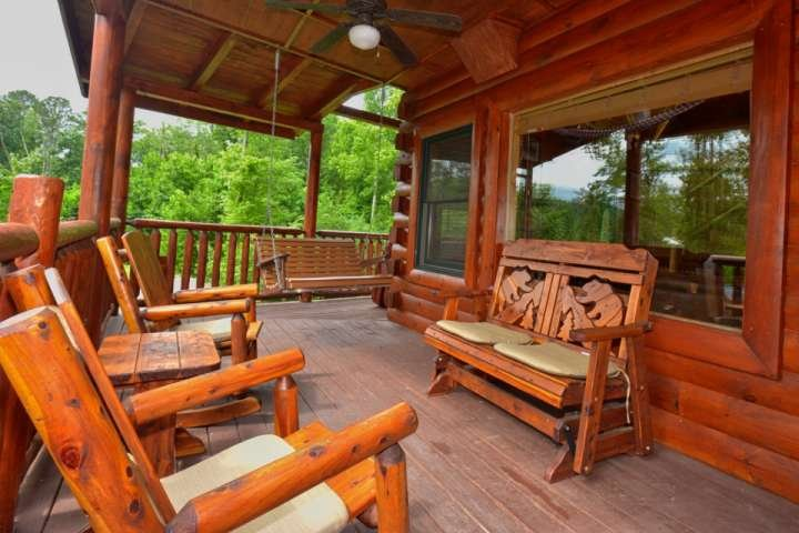 Lots of Room to Relax on the Wrap Around Porch at Kozy Lodge!  Porch Swing and Rockers are inviting after a long day shopping in Pigeon Forge