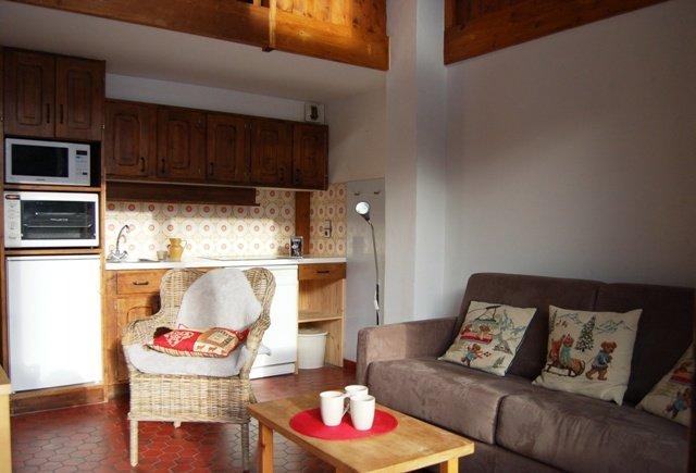Soggiorno con divano letto per due e una cucina con lavastoviglie