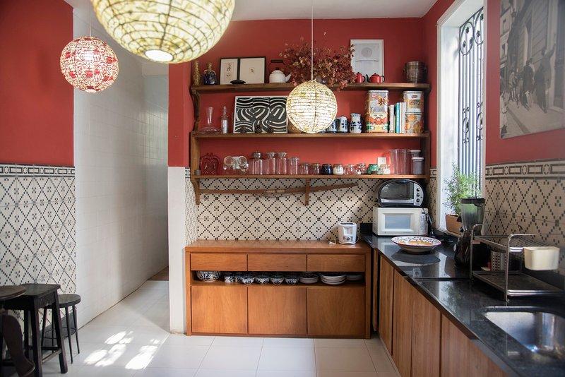 Die Küche mit 5-Flammen-Herd, Backofen, Mikrowelle, Kühlschrank, Geräten und einzigartigen Fenstern
