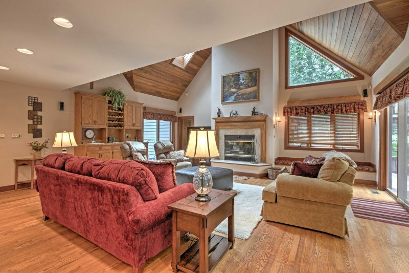 The living room features a cozy wood-burning fireplace, flat-screen cable TV and plush furnishings.