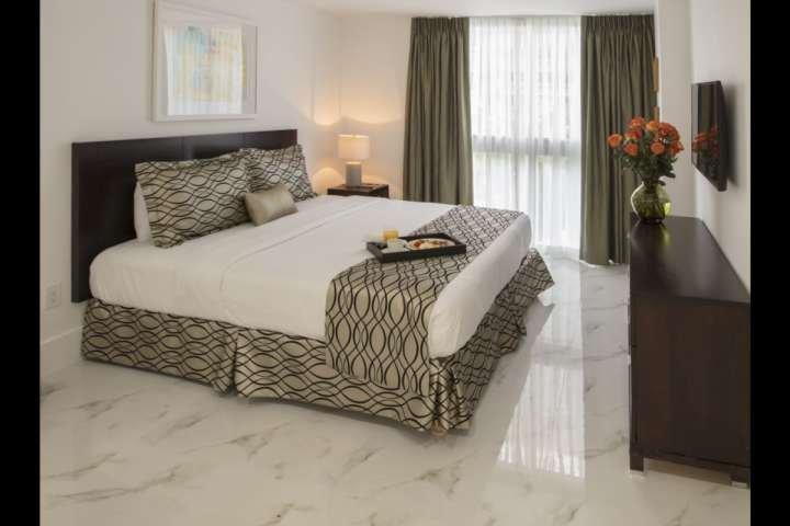 Elegant bedroom with king size bed, flat screen TV, and en suite bathroom.