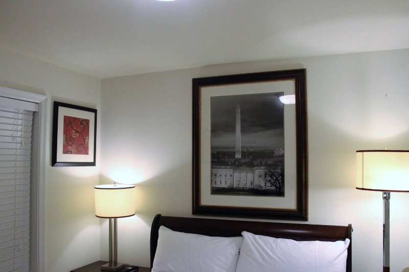 Cozy bedroom with nice pictures on walls, lovely lamps and white professionally laundered linen.