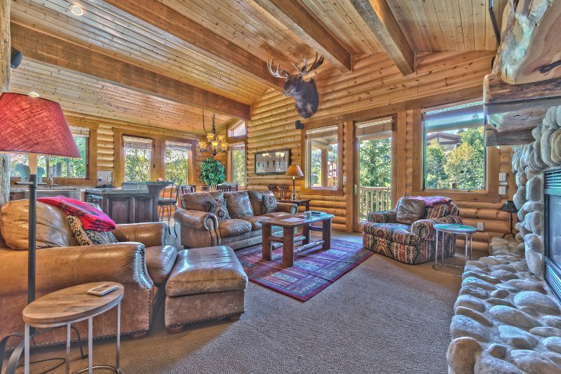 Spacious Living Room with Comfortable Mountain Furnishings, Queen Sofa Sleeper, Flat Screen TV and DVD, Gas Fireplace, and a Private Wrap Around Deck with Patio Seating and a Hot Tub