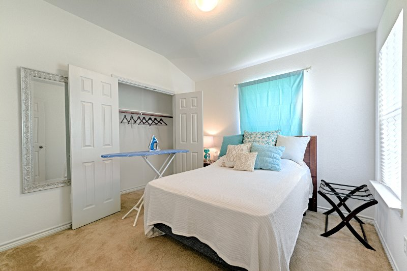 Private room with full-size bed and headboard, full-size mirror, night stand, lamp, luggage rack