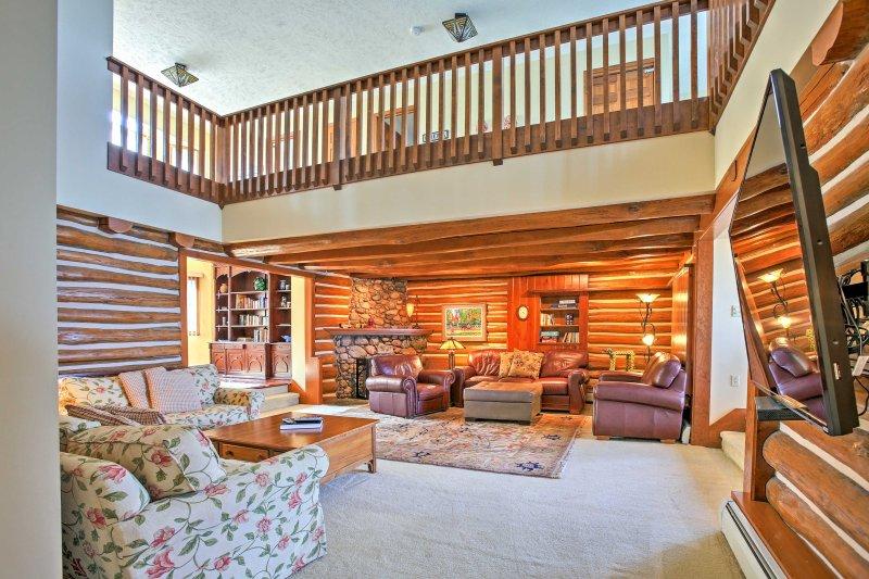 El salón cuenta con las paredes de madera originales de la casa de madera, 3 sillones de lujo, 2 sillones y TV por cable de pantalla plana de 60 pulgadas.