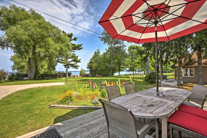 Enjoy a meal outdoors during your stay at this 5-bedroom, 3-bathroom vacation rental cottage in Suttons Bay!