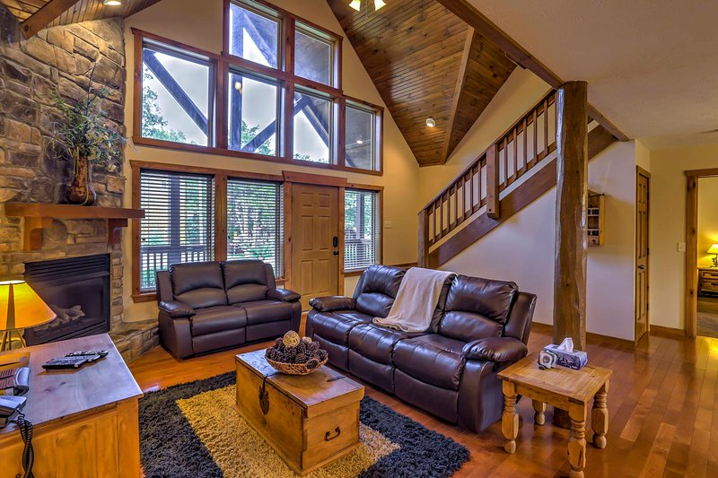 Relax on the leather couch in the living room during your stay at this 4-bedroom, 4-bathroom vacation rental cabin in Branson!