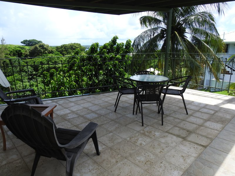 The covered pool terrace has a stunning sea view