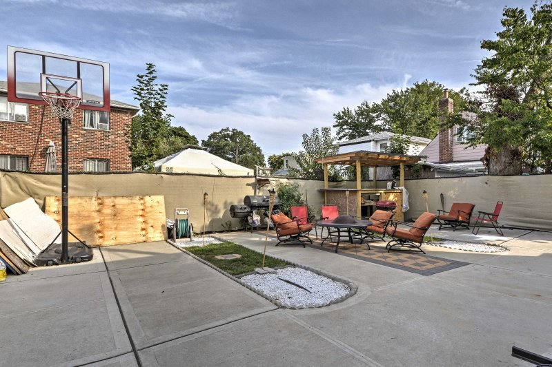 The enclosed yard features outdoor furniture, a fire pit and a basketball hoop.
