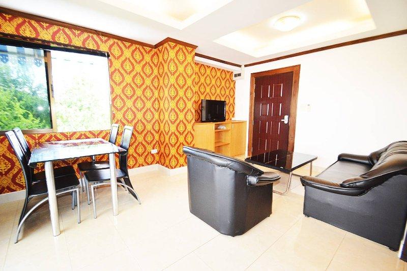 espaçosa sala de estar com poltrona extra e mesa de jantar