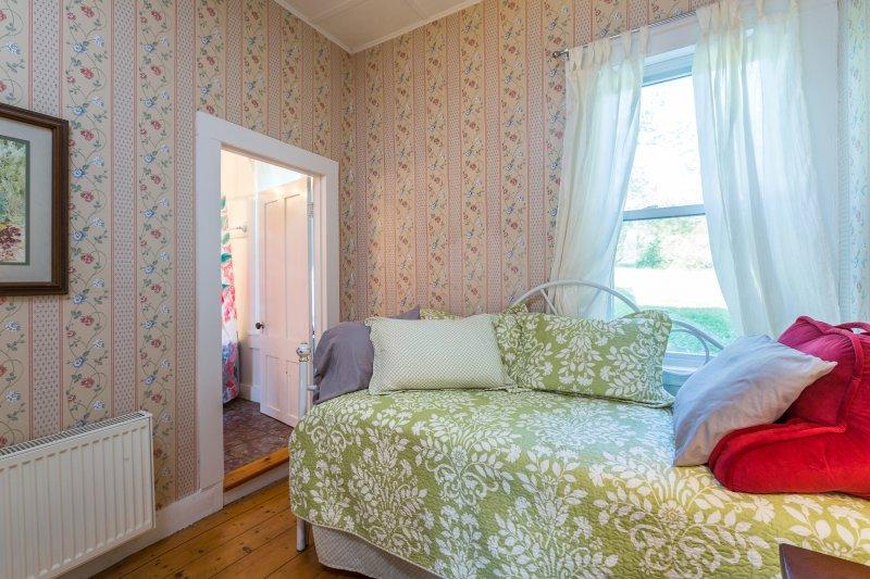 Der gemütliche Erdgeschoss Schlafzimmer hat einen Doppel-Schlafcouch mit zwei trundle.