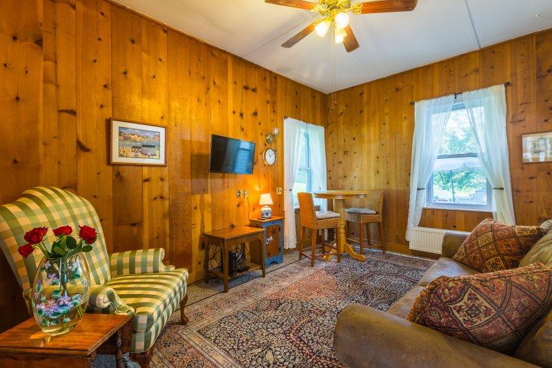 Sammeln Sie im Familienzimmer mit einem Plüsch-Sofa, Sessel, Kabel-TV und Bar Tisch.