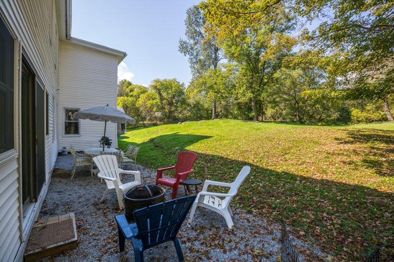 Entspannen Sie sich auf der hinteren Terrasse mit einem Tisch im Freien, Stühle, Sonnenschirm und Gasgrill.